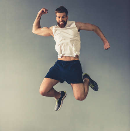 Foto de Handsome young bearded sportsman is showing muscles, jumping and smiling, on gray background - Imagen libre de derechos