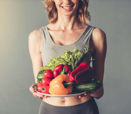 Foto de Beautiful young sportswoman is holding a plate with vegetables, looking at camera and smiling, on gray background - Imagen libre de derechos