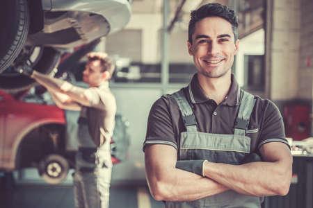 Foto de At the auto service. Handsome young auto mechanic in uniform is looking at camera and smiling while his colleague is examining car - Imagen libre de derechos