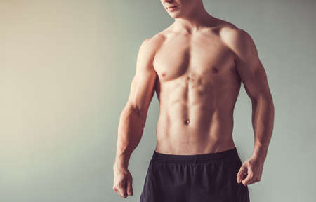Photo pour Cropped image of handsome muscular guy with bare torso, on gray background - image libre de droit