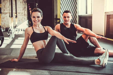 Photo pour Beautiful young sports couple is stretching after workout in gym - image libre de droit