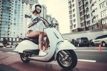 Foto de Beautiful girl in sun glasses and helmet is smiling while riding a scooter - Imagen libre de derechos