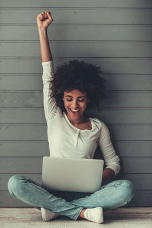 Photo for Attractive Afro American girl is using a laptop, raising hand in fist and smiling while sitting on the floor - Royalty Free Image