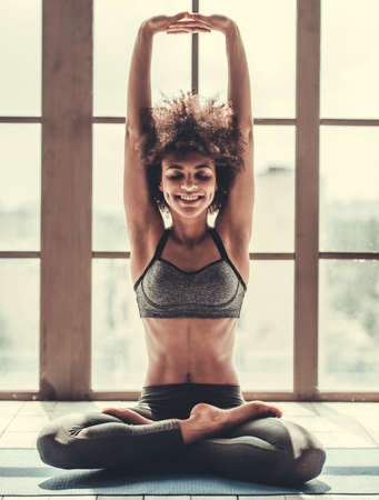 Photo for Attractive Afro American girl in sportswear is doing yoga and smiling - Royalty Free Image