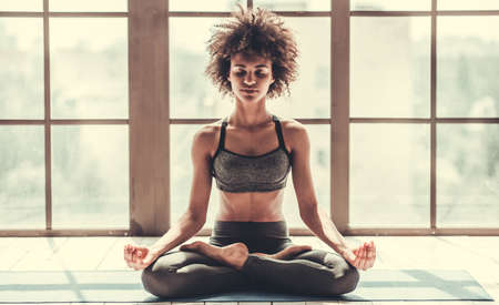 Photo for Attractive Afro American girl in sportswear is meditating while doing yoga - Royalty Free Image