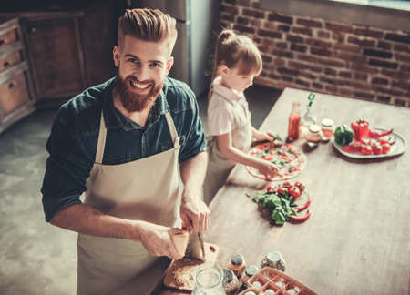 Foto de Cute little girl and her handsome bearded dad in aprons are smiling while cooking pizza in kitchen - Imagen libre de derechos