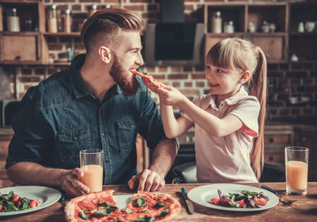 Foto de Cute little girl and her handsome bearded dad are smiling while drinking juice and eating pizza in kitchen - Imagen libre de derechos