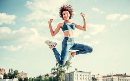 Photo for Beautiful Afro American girl in sportswear is looking at camera and smiling while jumping on city background - Royalty Free Image