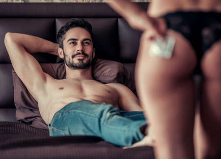 Foto de Couple having intimate moment. Handsome man is lying on bed and looking at sexy woman in black panties holding a condom - Imagen libre de derechos