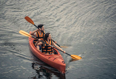 Photo for Happy young couple in sea vests is smiling while sailing a kayak - Royalty Free Image