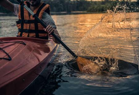 Photo pour Cropped image of handsome young man in sea vest sailing a kayak - image libre de droit
