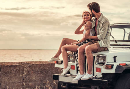 Photo pour Beautiful couple is hugging and smiling while sitting on their car - image libre de droit