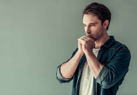 Photo pour Handsome young man in casual clothes is holding hands together like praying, on gray background - image libre de droit