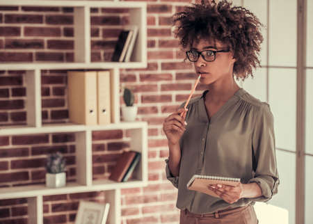 Beautiful Afro American business woman in smart casual wear and eyeglasses is thinking while standing with a notepad in office