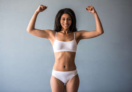 Photo pour Beautiful Afro American sports girl is showing her muscles, looking at camera and smiling, on gray background - image libre de droit