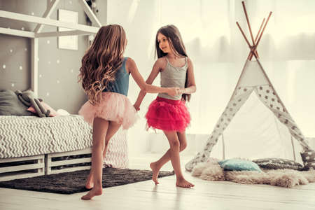 Photo for Two happy little girls are dancing and smiling while playing in children's room at home - Royalty Free Image
