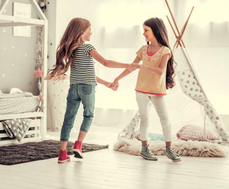 Photo pour Two happy little girls are dancing and smiling while playing in children's room at home - image libre de droit