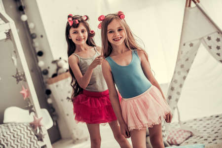 Foto de Two happy little girls in crowns are doing each other hair, looking at camera and smiling while playing in children's room at home - Imagen libre de derechos