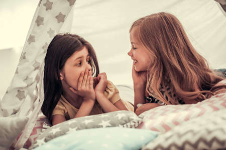 Photo pour Two cute little girls are talking and smiling while playing together in child's teepee - image libre de droit