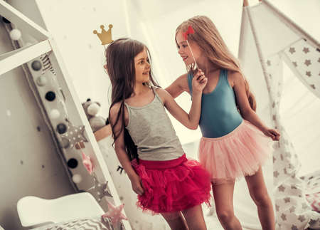 Photo pour Two happy little girls in crowns are holding party props, looking at each other and smiling while playing in children's room at home - image libre de droit