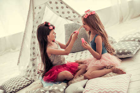 Photo for Two happy little girls in crowns are doing each other hair and smiling while playing in children's room at home - Royalty Free Image