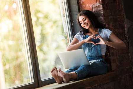 Photo for Beautiful Afro American girl in denim overall is using a laptop, showing a heart and smiling while sitting on the window sill at home - Royalty Free Image