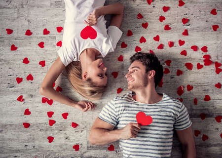Photo pour Top view of beautiful young couple holding red paper hearts, looking at each other and smiling while lying on the floor - image libre de droit