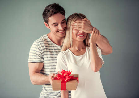 Foto de Handsome young man is holding a gift box and covering his girlfriend eyes making a surprise, both are smiling, on gray background - Imagen libre de derechos