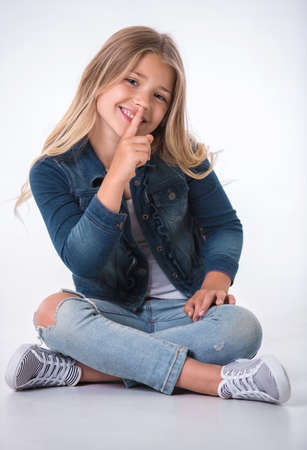 Photo for Beautiful little girl is showing silence sign, looking at camera and smiling while sitting on the floor on light background - Royalty Free Image