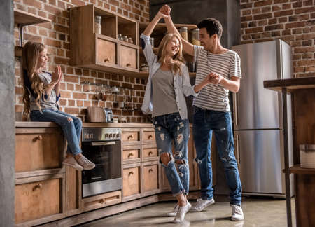 Foto de Cute little girl is looking at her beautiful parents dancing, all are smiling while spending time together in kitchen - Imagen libre de derechos