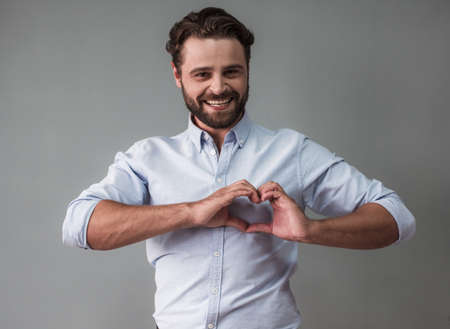 Photo pour Handsome bearded businessman in smart casual wear is showing a heart, looking at camera and smiling, on gray background - image libre de droit
