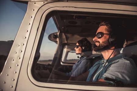 Foto de Beautiful couple in aviation headsets is sitting in aircraft ready to fly - Imagen libre de derechos