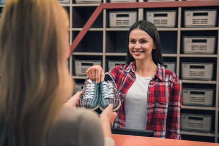 Foto de Beautiful girl is offering a pair of bowling shoes to the client and smiling - Imagen libre de derechos
