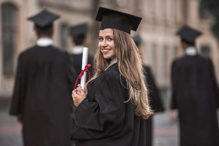 Foto de Beautiful female graduate in academic dress is holding diploma, looking at camera and smiling while standing outdoors - Imagen libre de derechos