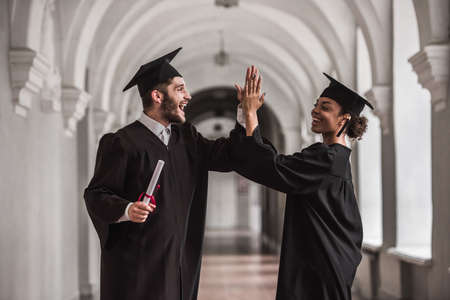 Photo pour Happy young graduates in academic dresses are holding diplomas,  giving high five and smiling while standing in university hall - image libre de droit