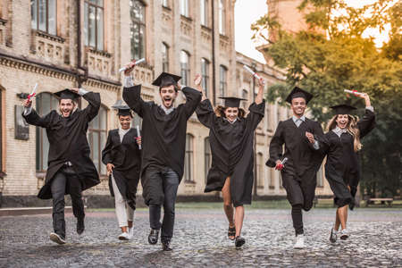 Photo for Successful graduates in academic dresses are holding diplomas, looking at camera and smiling while running outdoors - Royalty Free Image