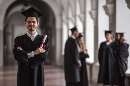 Photo for Successful graduates in academic dresses are talking in university hall, guy in the foreground is holding diploma, looking at camera and smiling - Royalty Free Image