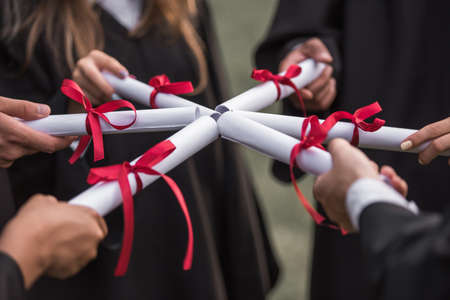 Photo pour Cropped image of successful graduates in academic dresses holding diplomas while standing outdoors - image libre de droit