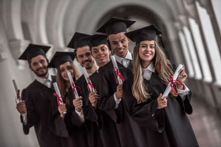 Photo pour Successful graduates in academic dresses are holding diplomas, looking at camera and smiling while standing in university hall - image libre de droit
