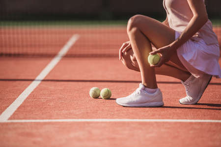 Photo for Cropped image of girl holding a tennis ball while playing tennis on court outdoors - Royalty Free Image