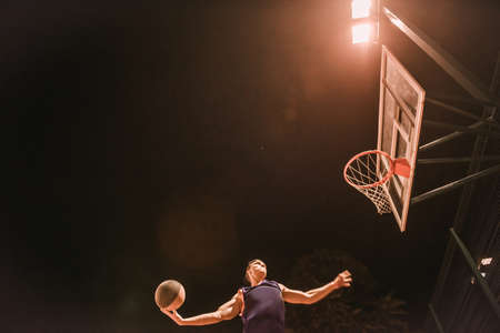 Photo pour Stylish young basketball player in cap is jumping and shooting a ball through the hoop while playing outdoors at night - image libre de droit