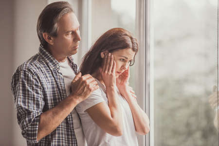 Foto de Couple at home. Handsome mature man is calming his upset wife while both are standing near the window - Imagen libre de derechos