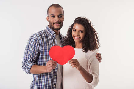 Photo pour Beautiful Afro American couple holding a big red paper heart, looking at camera and smiling, isolated on white background - image libre de droit