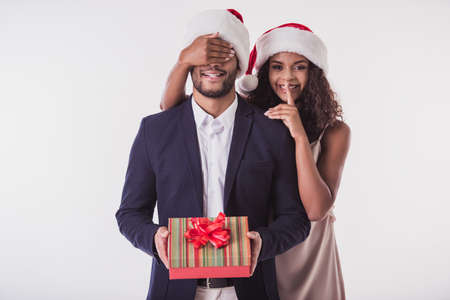 Foto de Elegant Afro American couple in Santa hats. Beautiful is covering her boyfriend's eyes, showing silence sign, looking at camera and smiling, isolated on white - Imagen libre de derechos