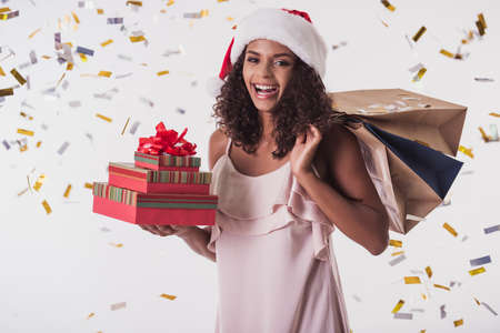 Photo for Beautiful Afro American girl in dress and Santa hat is holding presents, looking at camera and smiling, isolated on white - Royalty Free Image