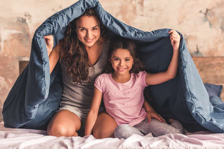 Photo pour Beautiful mom and daughter are looking at camera and smiling while sitting on bed covered with a duvet - image libre de droit