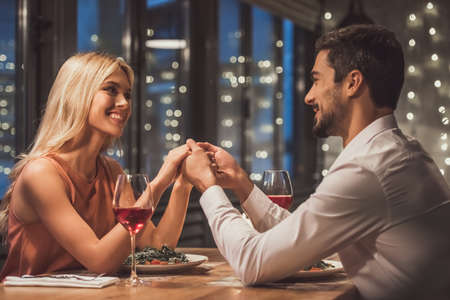Photo for Beautiful young couple is looking at each other, holding hands and smiling during their date in a restaurant - Royalty Free Image