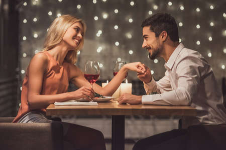 Photo for Beautiful young couple is looking at each other and smiling during their date in a restaurant, man is holding his girlfriend's hand - Royalty Free Image
