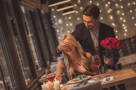 Photo pour Handsome elegant man is holding roses and covering his girlfriend's eyes while making a surprise in restaurant, both are smiling - image libre de droit