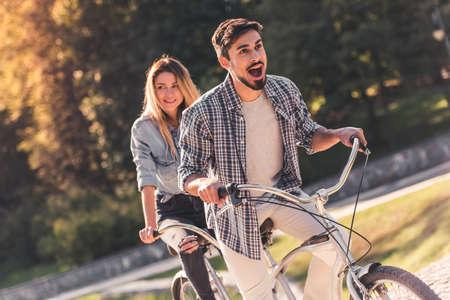 Foto de Beautiful young couple is having fun while riding a tandem bicycle in the park - Imagen libre de derechos